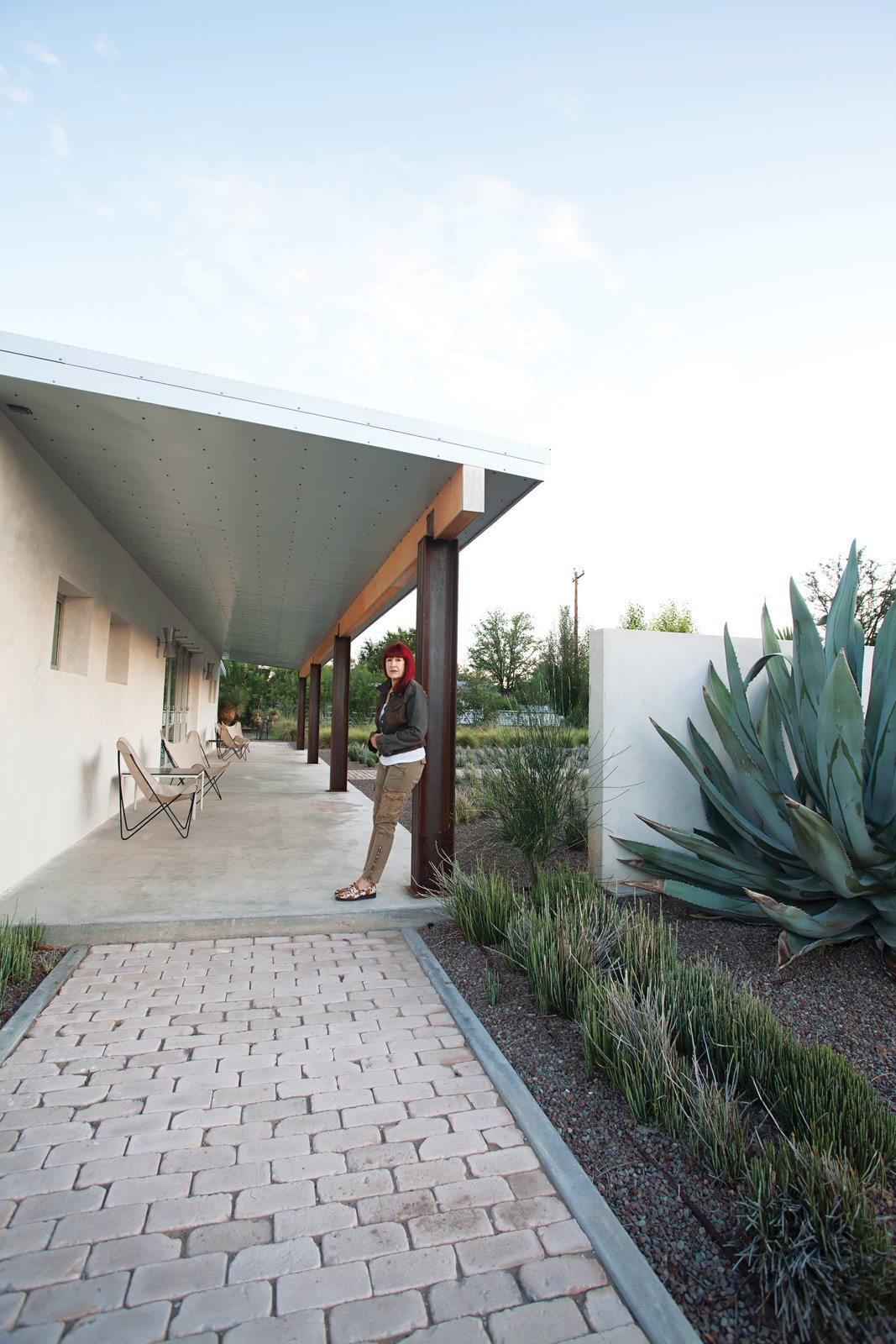 Designer Barbara Hill, in front of her recently renovated weekend house in Marfa, Texas. A series of Galvalume roofing panels clad the underside of the eaves.
