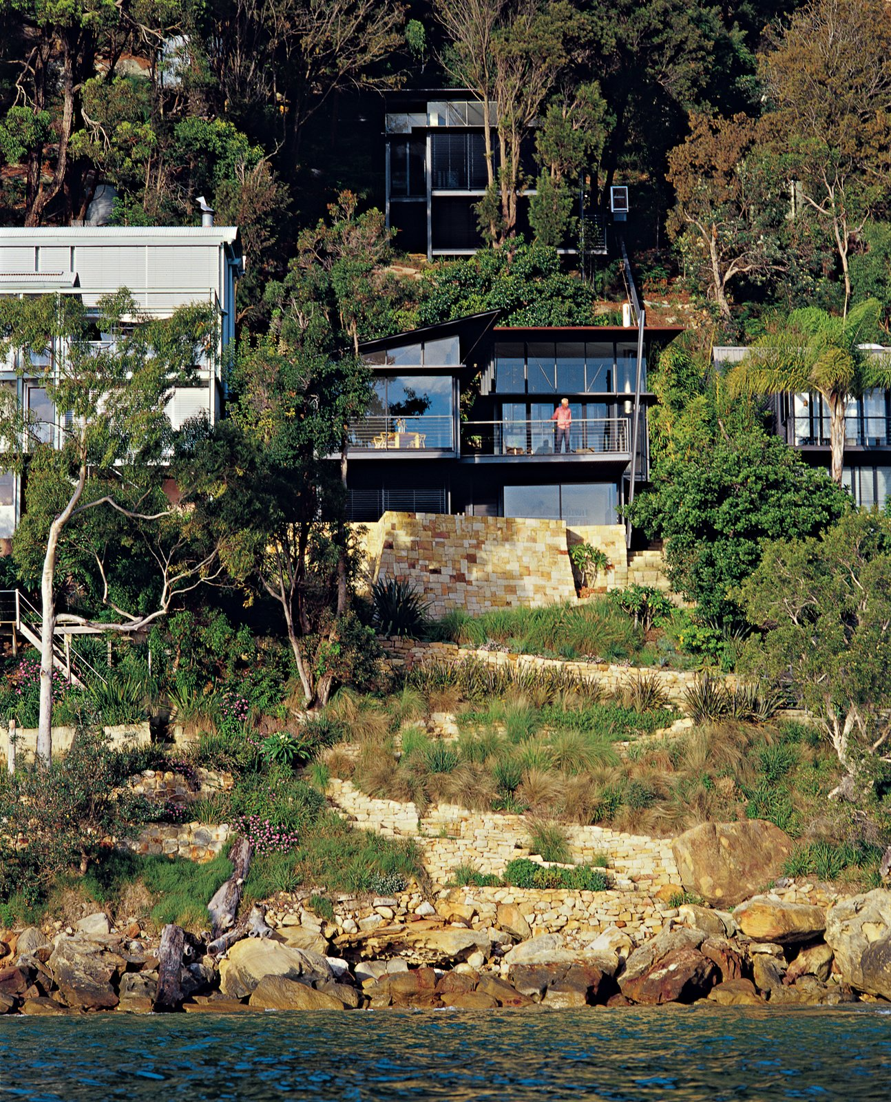Set high on a cliff along the south end of the beach, this residence of three glass-and-copper pavilions offers a mighty reward for conquering the steep ascent. Tagged: Outdoor, Slope, Trees, Shrubs, and Boulders.  Photo 5 of 11 in Three Glass-and-Copper Pavilions Conquer the Cliffs