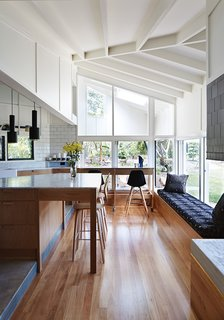 This Kitchen Brings It All Together - Photo 3 of 4 - The architects used blackbutt wood for the flooring and Whisper White paint by Dulux throughout the interior. An A110 Hand Grenade Pendant Lamp, by Alvar Aalto for Artek, hangs above the white Carrara marble-topped island.