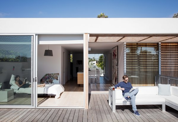Tracy and Thaddeus enjoy an afternoon read from the master bedroom and terrace, respectively; the outdoor sectional is by Gandia Blasco.