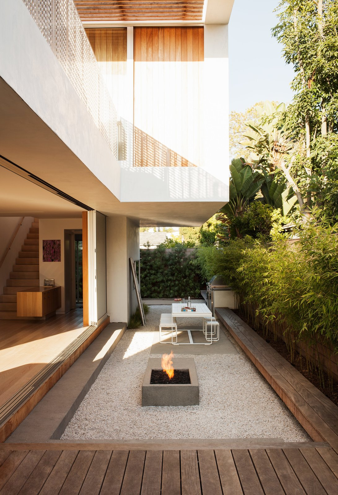 The outdoor living room serves as both a counterpoint and extension of the interior, with amenities that include a Gandia Blasco dining table and bench, a Lynx grill, and a custom concrete fire pit designed by Kathleen Ferguson; it sits atop a bed of crushed white rock. A built-in bench runs along the length of the courtyard. Tagged: Outdoor, Stone Patio, Porch, Deck, Wood Patio, Porch, Deck, and Back Yard.  Photo 11 of 13 in Get Your Tongs Ready For the Long Weekend With 13 Outdoor Spaces Made For Grilling from Amid a Hotbed of Architecture, This Home Holds Its Own