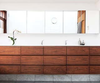 A 1930s Tudor Home Brightens Up in Toronto - Photo 1 of 12 - Architect Paul Syme designed custom storage units with dark-stained walnut fronts that provide a place for everything in his clients' Toronto bathroom. The wall-to-wall mirror and the Corian counter are custom, and the faucets are by Vola.