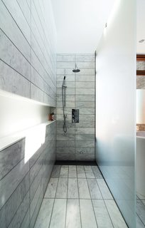 "A 1930s Tudor Home Brightens Up in Toronto - Photo 4 of 12 - The standing shower is set off by etched-glass panels supported by stainless-steel hardware. There is no threshold; instead, the tile within the shower zone slopes down very slightly to a floor trough with a custom stainless-steel grille. Along the wall, a Corian shelf—""the longest soap dish in the world,"" resident Don Evans jokes—runs the length of the space."