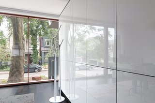 A 1930s Tudor Home Brightens Up in Toronto - Photo 9 of 12 - On the ground floor, freestanding cabinetry with a gloss lacquer finish by Bulthaup separates the entryway from the kitchen and dining area.