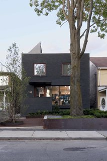 A 1930s Tudor Home Brightens Up in Toronto - Photo 11 of 12 - The transformed facade features dark gray stained-masonry.
