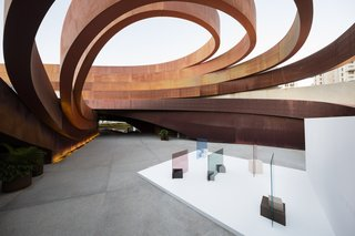 "Nendo's Minimalism Meets Ron Arad's Sweeping Curves - Photo 2 of 7 - The courtyard contains a site-specific installation called ""In the Shade"" that features sheets of colored glass by Glas Italia anchored by Caesarstone pedestals."