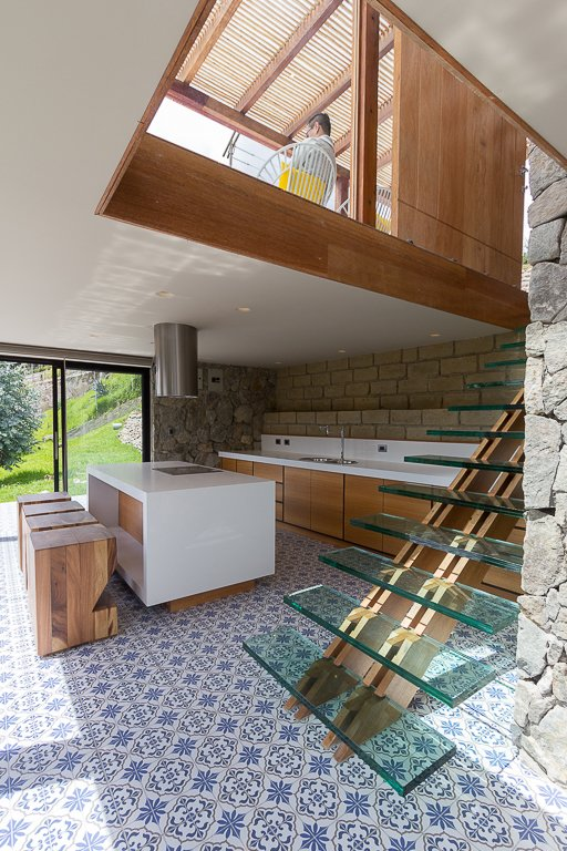 In the kitchen, a staircase with a wood backbone supports floating glass treads. The home's main entrance is located on the top level, due to the property's incline. Tagged: Staircase.  K I T C H E N S by Creative Designer from Tourists to Ecuador Hope to Get Near This Home's Lookout