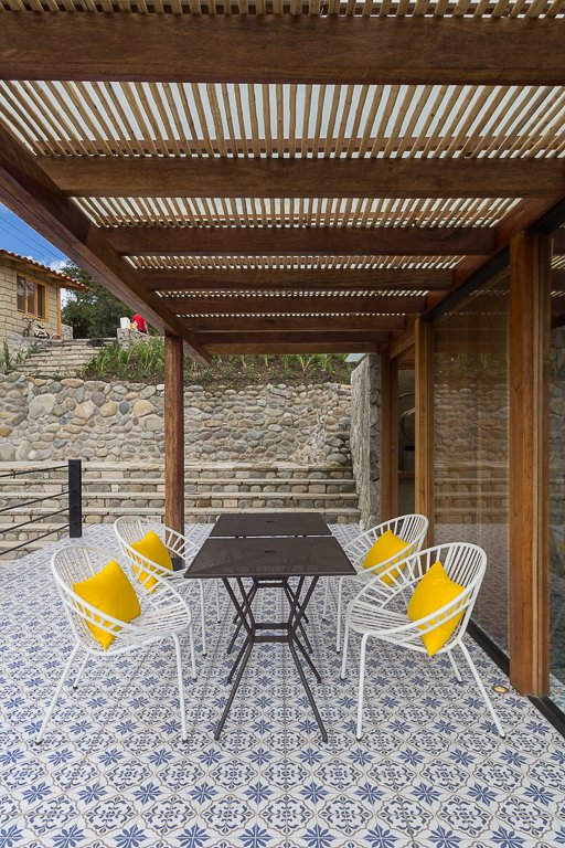 Visitors cross a tile deck underneath a pergola to enter.  Pergolas by Natalie Pinkerton GRI from Tourists to Ecuador Hope to Get Near This Home's Lookout