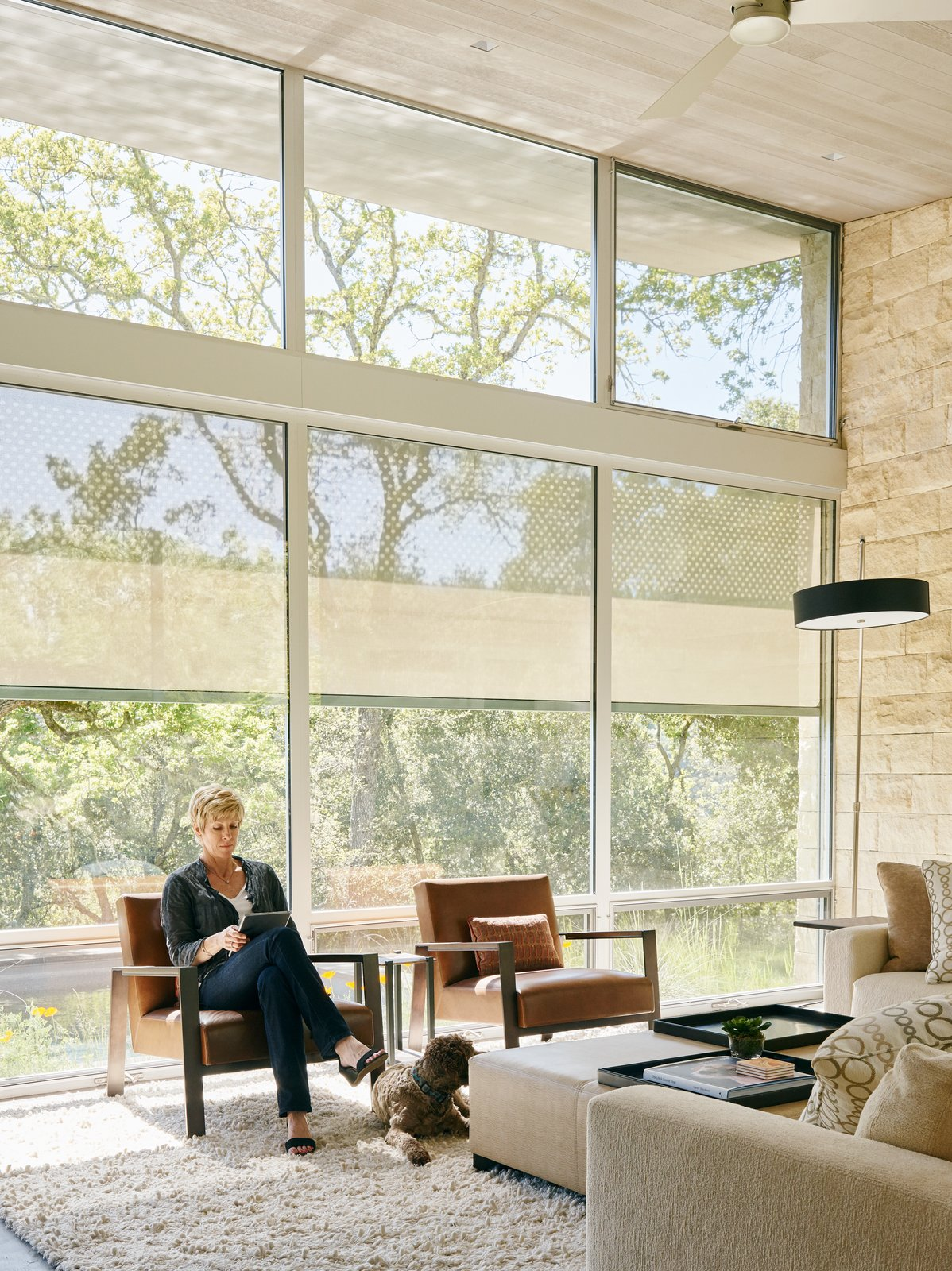 A Savant system gives the residents centralized control of the lighting, heating, audio, and more. Mitcie unwinds in a Linden chair by Holly Hunt in the living room.