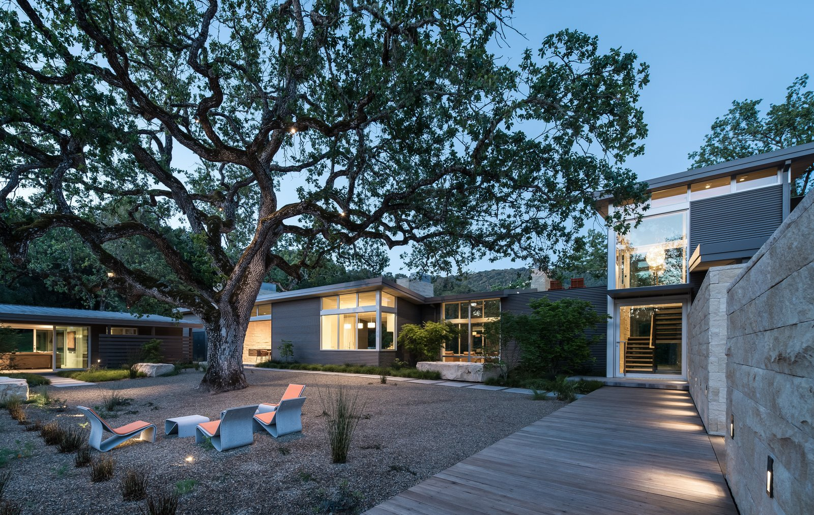 """""""The lone valley oak in some ways defined the shape of the house,"""" says landscape architect Bernard Trainor. The structure wraps around the century-old tree, forming a courtyard with a series of fiber-cement chairs by French designer Julia von Sponeck. Tagged: Outdoor, Back Yard, Side Yard, Front Yard, Trees, Landscape Lighting, and Shrubs.  Photo 5 of 6 in 8 Inspirational Quotes to Stay Innovative from A Meadow With Amenities"""