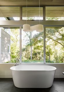 A Meadow With Amenities - Photo 8 of 10 - In the master bath, a Duna pendant by El Torrent hangs above a Blu Stone tub.