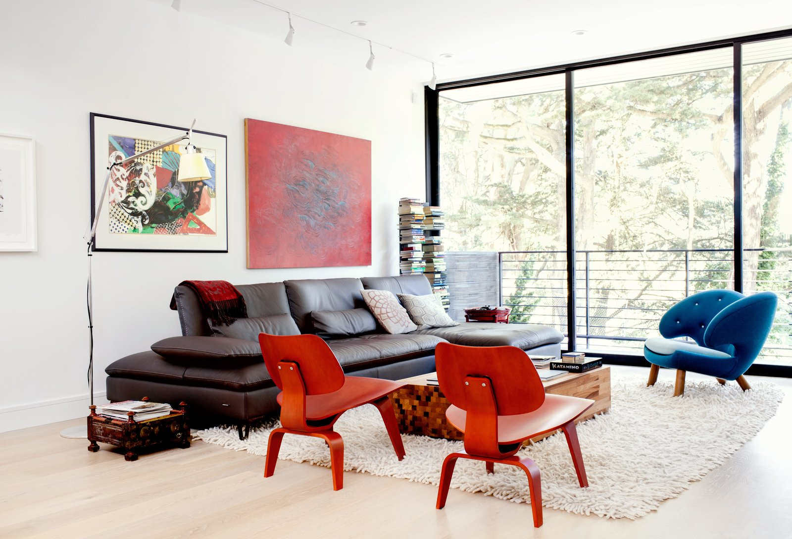 """The main floor is arranged as one long, contiguous space, with a living area and balcony at the front end. An Aulia coffee table by Henk Vos, a pair of red Eames molded plywood chairs, and a Pelican chair by Finn Juhl center the space. Tagged: Living Room, Chair, Sofa, Floor Lighting, and Light Hardwood Floor.  Photo 3 of 12 in Two Silicon Valley Vets Master the Smart Home Without Going Full """"Jetsons"""""""