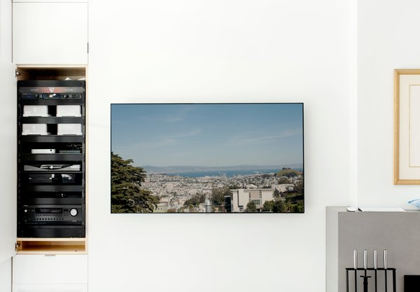 From the gray leather Roche Bobois sofa, one can take in a view of the surrounding city via a television wired to a rooftop camera. The control center for the home's automation systems is concealed inside a nearby cabinet.