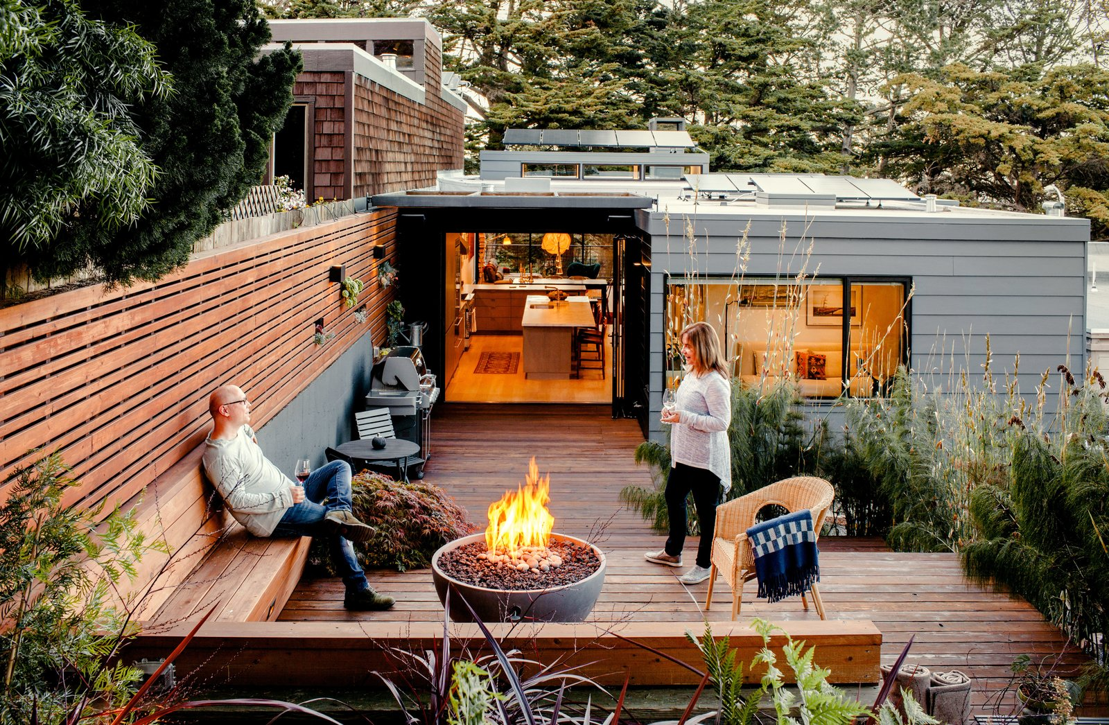 "After raising the rear patio to the level of the kitchen, the team reused the original redwood decking and supplemented it with recycled pieces from other projects. Recessed planters punctuate a garden wall. Scott and Regina warm themselves by a Solus fire pit on chilly evenings. Tagged: Outdoor, Small Patio, Porch, Deck, Wood Patio, Porch, Deck, and Back Yard.  Photo 6 of 12 in Two Silicon Valley Vets Master the Smart Home Without Going Full ""Jetsons"""