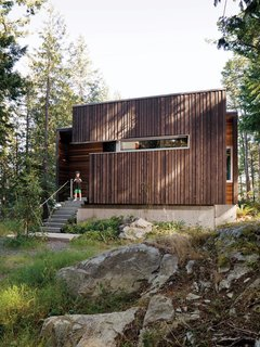 The facade is clad with beveled siding, stained dark to meld into the forest.