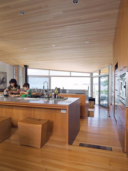 Lam and her son Max prepare a snack together in the open-plan kitchen at the center of the house. The fir floor that covers the living space steps downward twice, creating a grade change that roughly follows the topology of the site. The ceiling is sheathed in untreated hemlock; the custom stools were designed by Brent Comber.