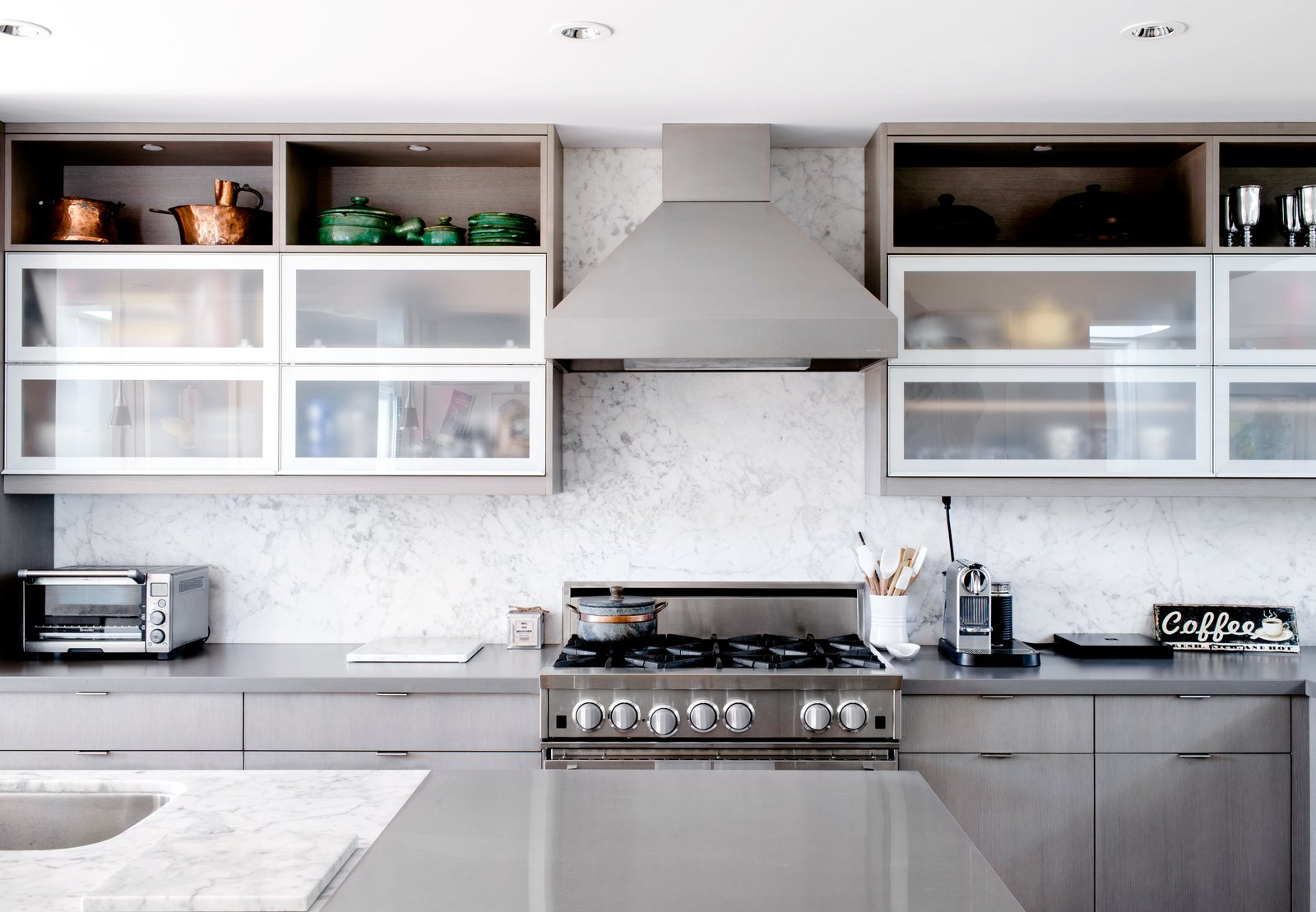 "The search for a 13-foot-long island to fit their kitchen led them to marry Calacatta Miele and stainless steel to make one giant counter. Marble, they discovered, was available only in 10-foot slabs, due to the dimensions of shipping containers. Tagged: Kitchen, Metal Counter, Ceiling Lighting, Marble Counter, Marble Backsplashe, Range, and Range Hood.  Photo 7 of 12 in Two Silicon Valley Vets Master the Smart Home Without Going Full ""Jetsons"""