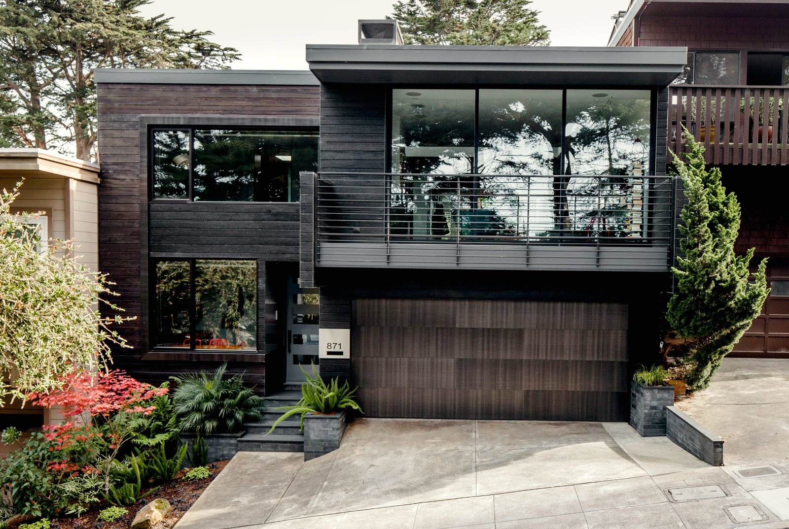 "Scott MacFiggen and Regina Bustamante, tech industry veterans from Silicon Valley, called on architect Christi Azevedo to rebrand a fusty house in San Francisco's Noe Valley, starting with the street view. Cedar boards, charred using the Japanese technique shou sugi ban, replaced plywood siding. Tagged: Exterior, House, Metal Roof Material, Wood Siding Material, and Flat RoofLine.  Photo 2 of 12 in Two Silicon Valley Vets Master the Smart Home Without Going Full ""Jetsons"""