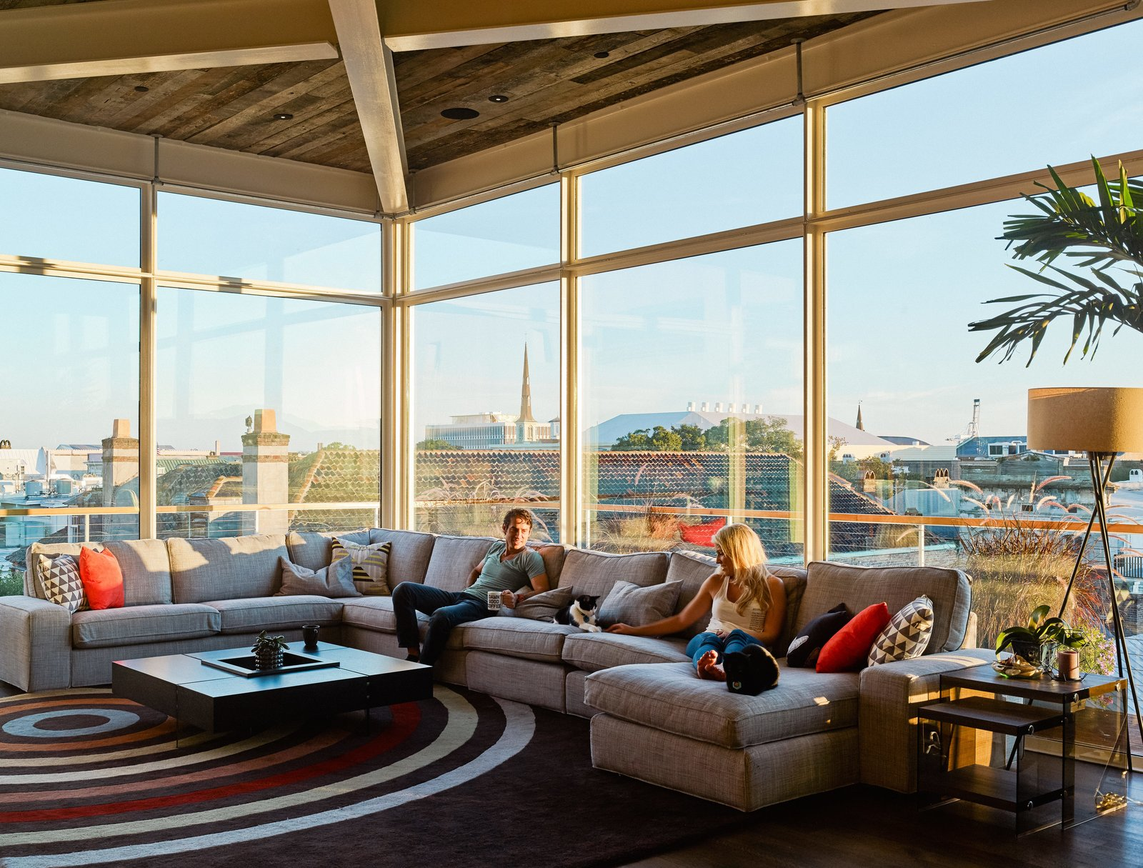 Rich and his girlfriend Arielle sit on an IKEA sofa; the windows are from Charleston Glass. Tagged: Living Room, Sectional, Coffee Tables, and Floor Lighting.  Photo 5 of 8 in High Above Traditional Charleston, a Modern Home Finds its Roost