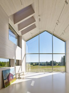 """This Battery-Powered House Never Runs Out of Juice - Photo 2 of 7 - Elina works beneath a series of skylights and LED spots from Zumtobel in her studio. <span style=""""line-height: 1.8;"""">At more than 16 feet tall, the locally fabricated windows benefit from aluminum frames, which can be substantially thinner than wood versions.</span>"""