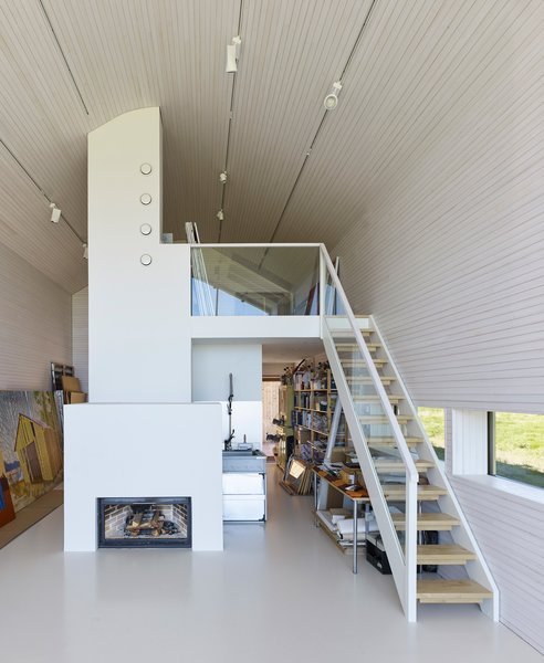 The studio fireplace is a custom design by OOPEAA, and one of the elements that will allow the house to go off the grid.