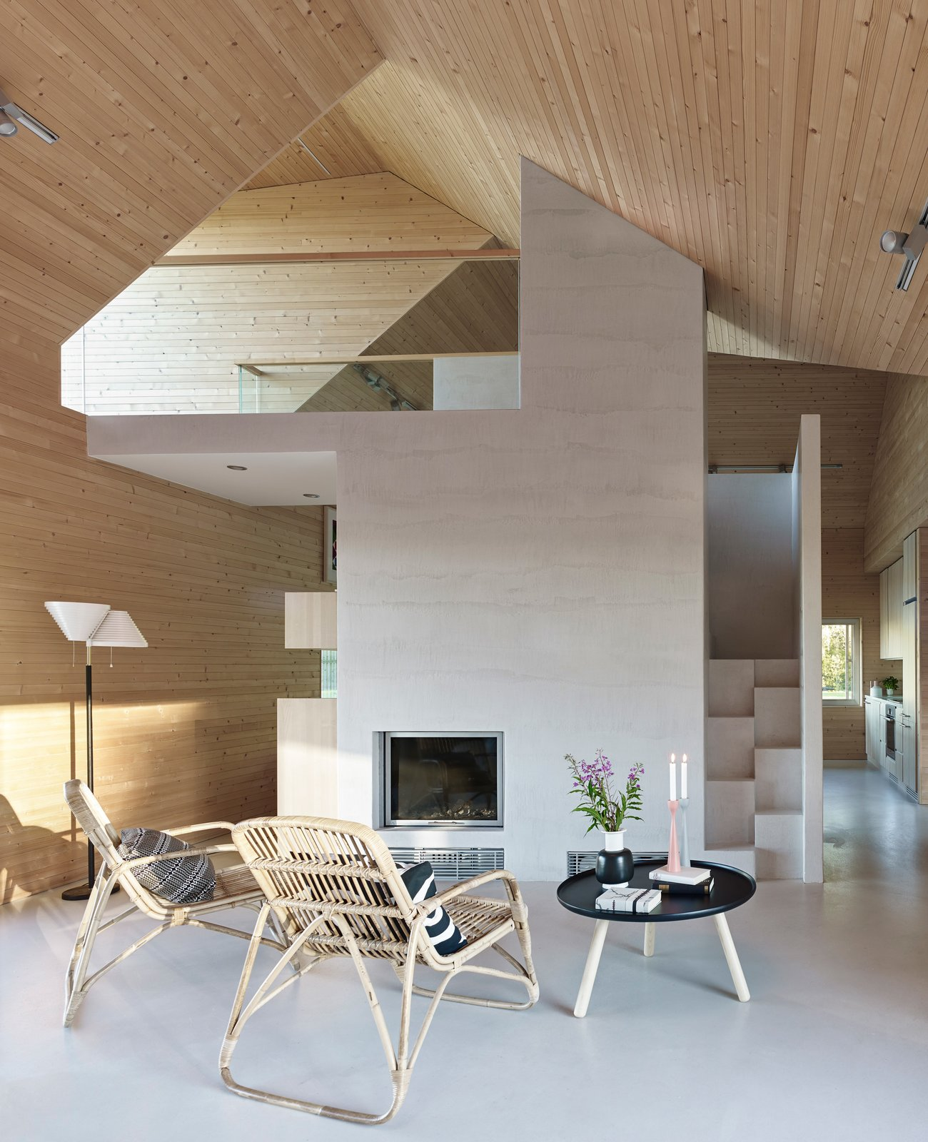 The living room includes a table from Normann Copenhagen, chairs by Annansilmät-Aitta, and Alvar Aalto's A810 lamp for Artek, all on a poured concrete floor.  Photo 5 of 8 in This Battery-Powered House Never Runs Out of Juice