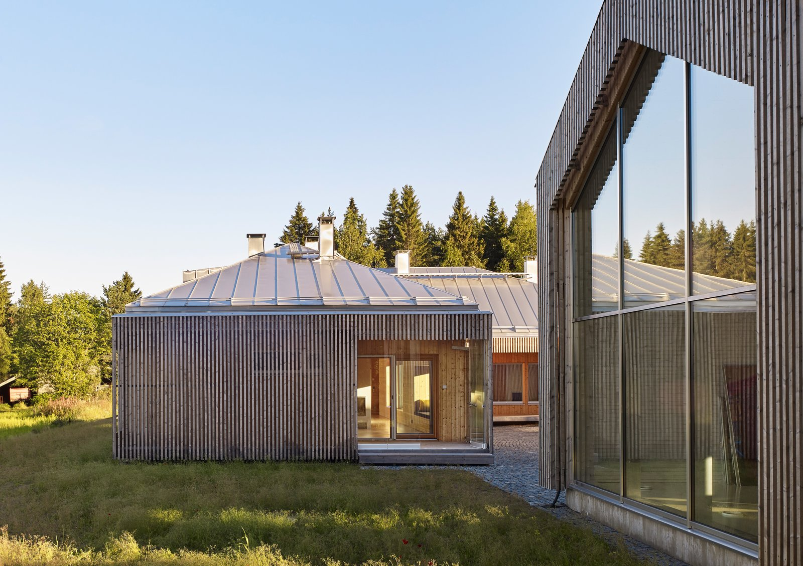 """The home comprises three structures: a main house, a garage, and a studio for resident Elina Försti, an artist. Local spruce cladding, metal standing-seam roofs, and aluminum frames mean the entire complex is recyclable. """"Right now, it all looks very polished, but in the future it will develop a nice patina,"""" Lassila says.  Photo 6 of 8 in This Battery-Powered House Never Runs Out of Juice"""