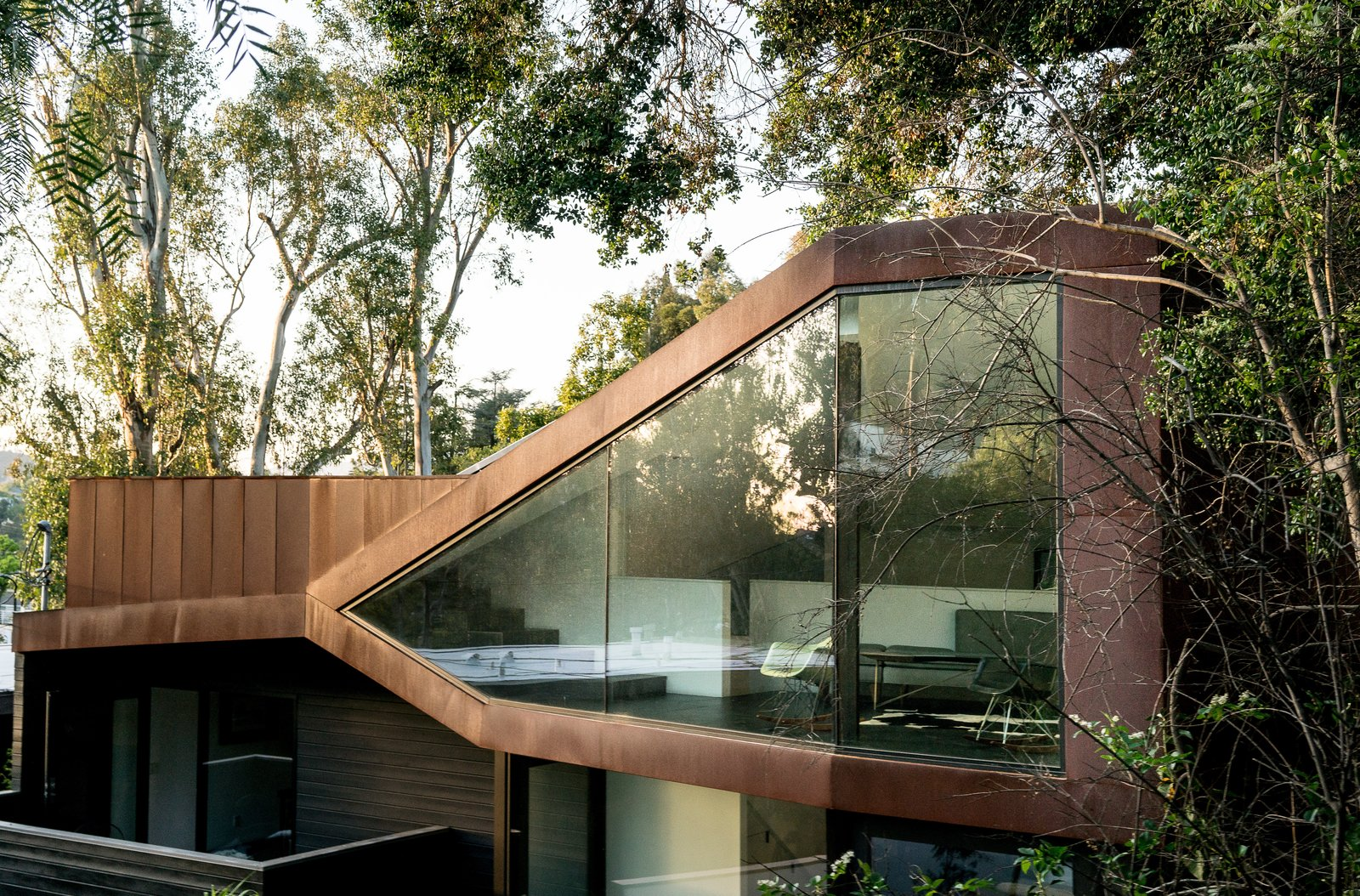 """Resident Richard Kim, who works as the head of design at electric car company Faraday Future, tested his know-how with the creation of his own Los Angeles home, a curvilinear structure clad in Cor-Ten steel and black-stained cedar. """"This house is different,"""" says Richard. """"It's as much a sculpture as it is a place to live."""" Tagged: Exterior, House, Glass Siding Material, Metal Siding Material, Metal Roof Material, and Wood Siding Material.  Photo 2 of 10 in This Los Angeles Home is Driven by Automotive Design"""