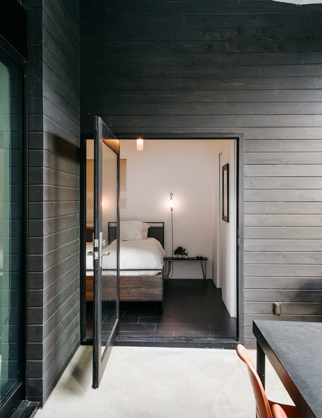 The patio is accessed from the master bedroom via a large pivot door. The bed and mirror are from Crate and Barrel; the pendant is from Droog. The couple made the wall sconces themselves.