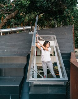 This Los Angeles Home is Driven by Automotive Design - Photo 7 of 9 - Kristine climbs out onto the concrete-tile roof deck through a hatch door in the upstairs loft.