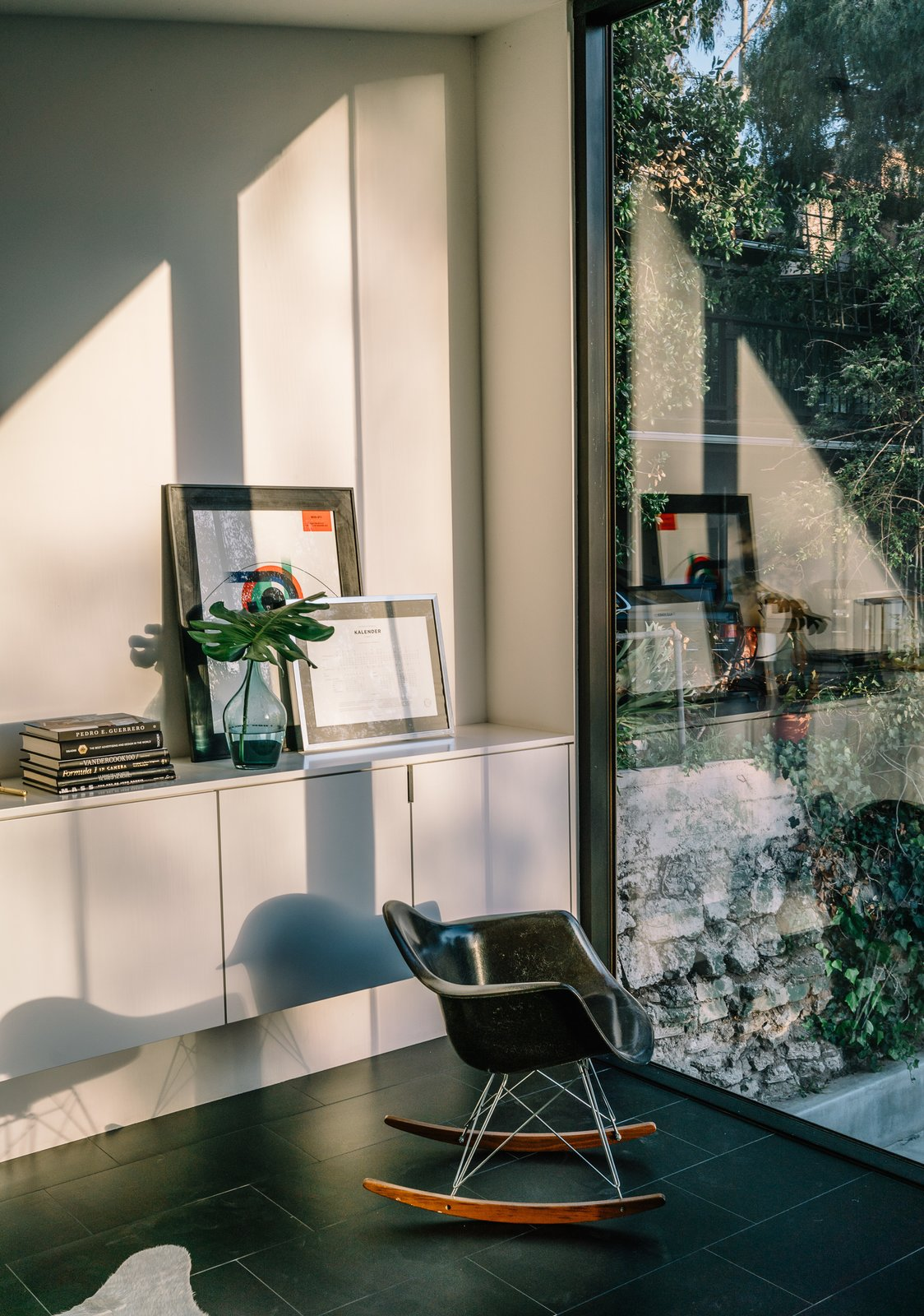 The home's deep setback from the street means the couple can leave the large windows undressed to maximize light throughout the day Tagged: Living Room, Chair, Storage, and Ceramic Tile Floor.  Photo 9 of 10 in This Los Angeles Home is Driven by Automotive Design