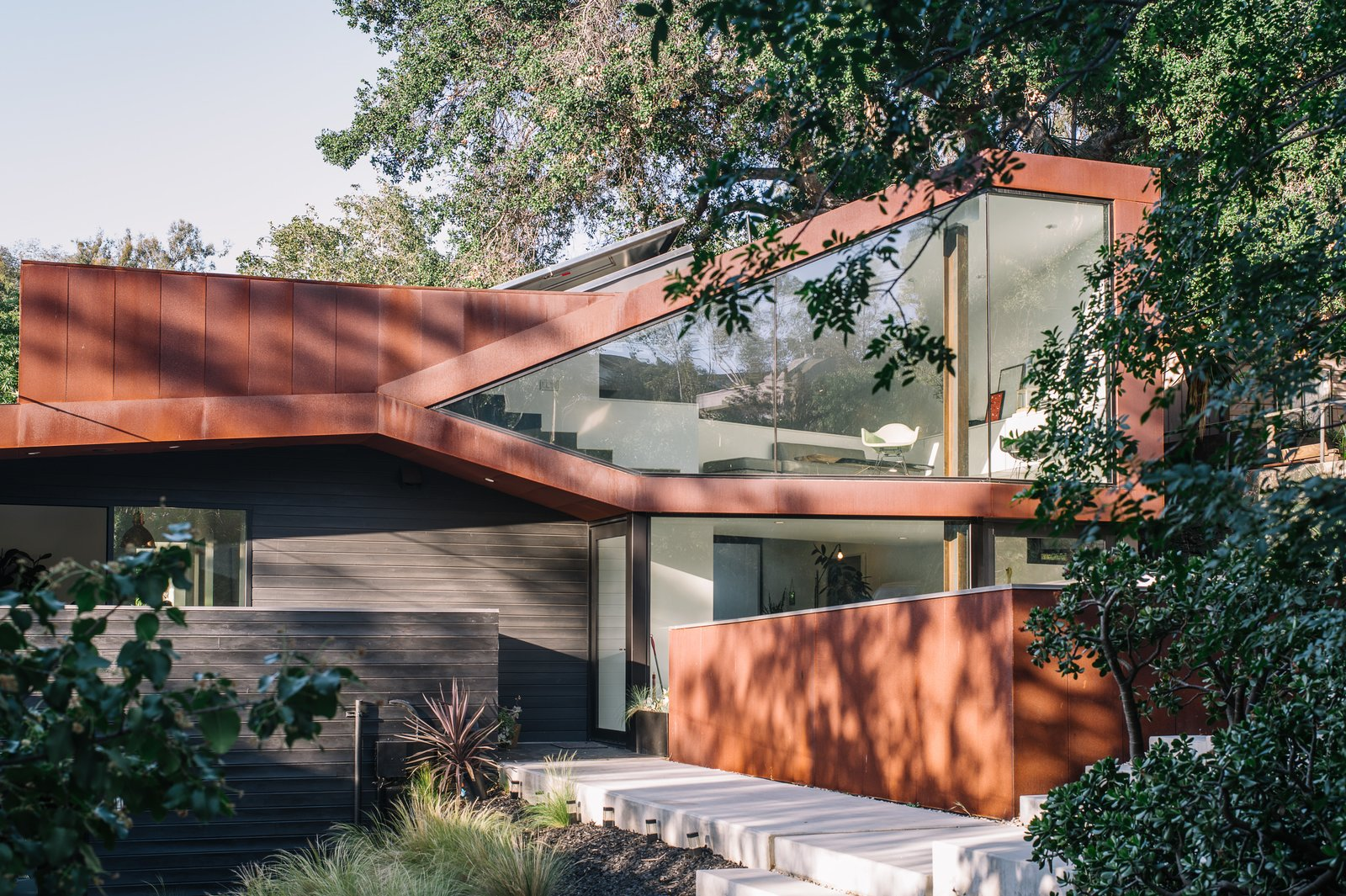 Resident Richard Kim, who works as the head of design at electric car company Faraday Future, tested his know-how with the creation of his own Los Angeles home, a curvilinear structure clad in Cor-Ten steel and black-stained cedar. Tagged: Exterior, House, Metal Siding Material, Wood Siding Material, Glass Siding Material, and Metal Roof Material.  Photo 1 of 10 in This Los Angeles Home is Driven by Automotive Design