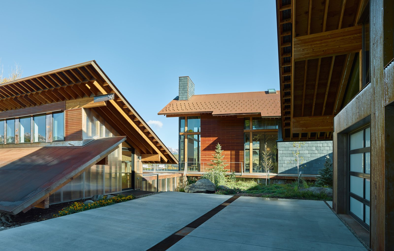 Architect Doug Wells and his wife, Sarah, jumped at the chance to turn a former homeowners' association clubhouse in Colorado into a vacation retreat. The existing structure is flanked by two new prefab buildings: a garage and a main house.  Modern Homes in Colorado by Luke Hopping from Self-Regulating Technology Makes Managing This Compound a Breeze
