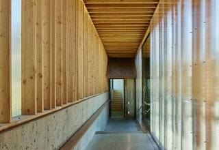 Self-Regulating Technology Makes Managing This Compound a Breeze - Photo 3 of 8 - Simple passageways with polycarbonate glazing, wood framing, and polished concrete floors connect the structures.