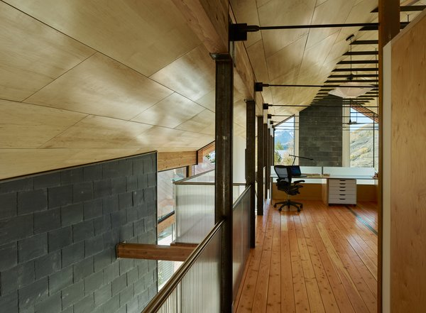 In the main house, a lofted upper level contains the master suite and an office area, furnished with an Aeron chair from Herman Miller.