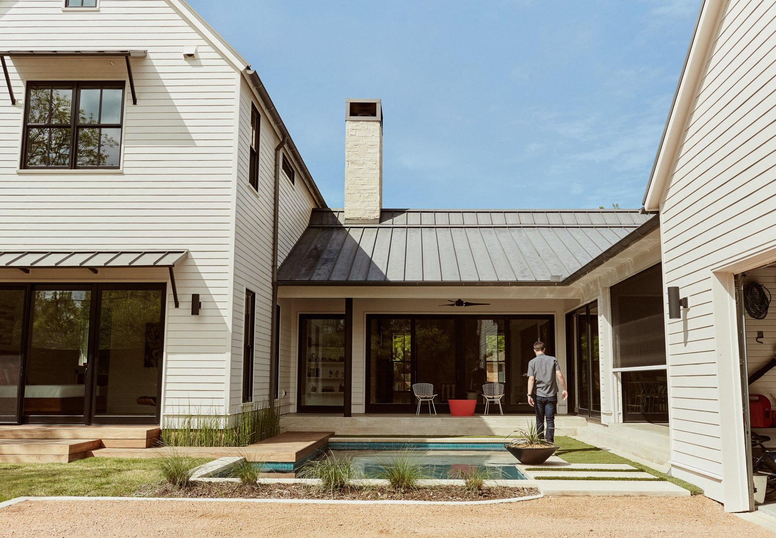 Homeowners Matthew and Lindsay Thomas, who build houses for a living, worked with architects Todd Hamilton and Scott Slagle to create their own residence—a vernacular form characterized by horizontal clapboard cladding and a standing-seam, paint-grip roof.  Photo 9 of 9 in Boards, Battens, and Bevels: Wood Board Siding Types and Their Uses from Automation Eliminates Tedious Chores for Dallas Homeowners