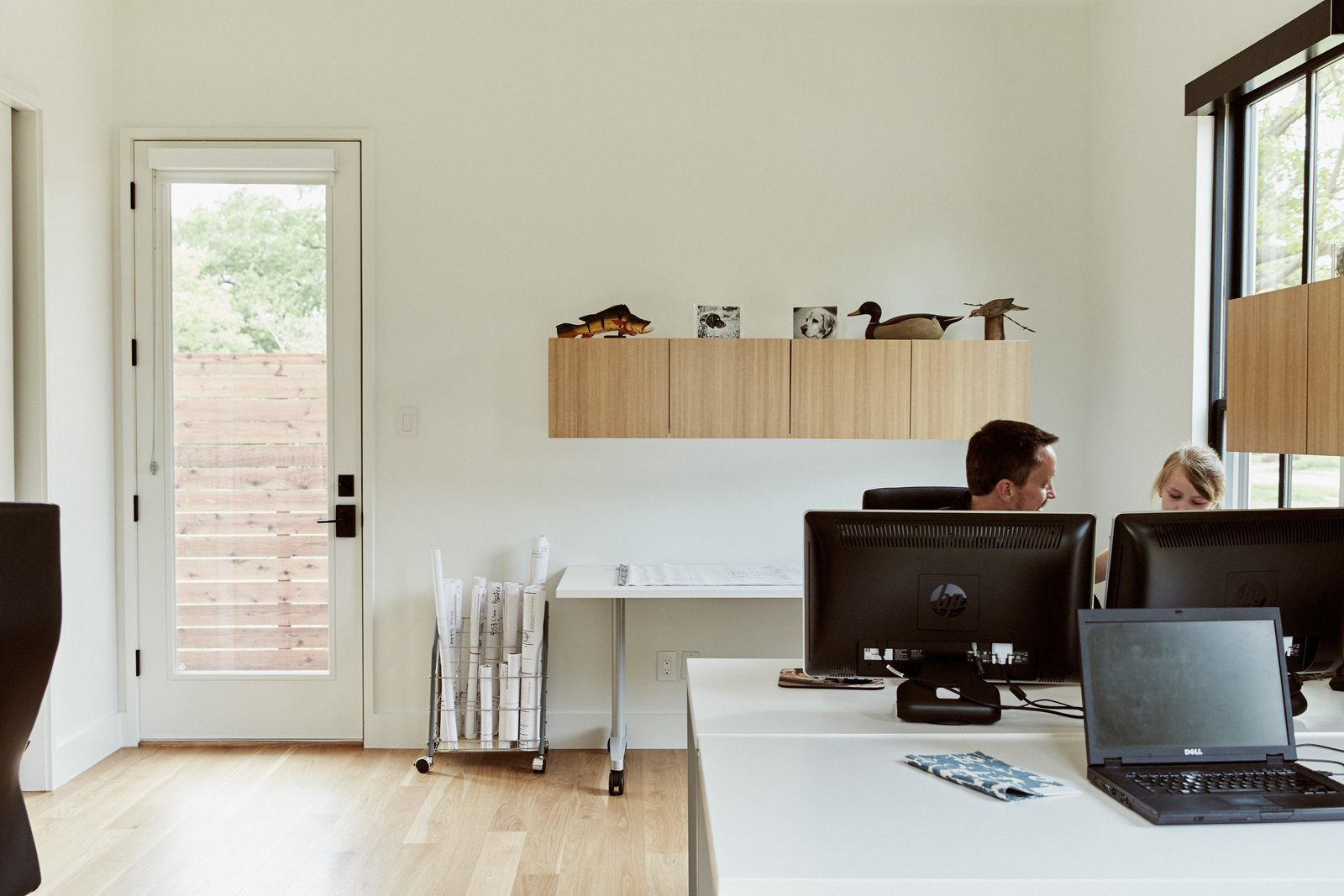 The two-story structure includes a simple office furnished with desks and cabinets by Hon Voi (below). Nearly all of the home's 29 windows—which help keep cooling and lighting costs to a minimum—are controlled via the RTI app, which consolidates nearly a dozen apps from Lutron, Honeywell, and others. Tagged: Office, Study, Bookcase, Storage, Chair, Shelves, Desk, and Light Hardwood.  Best Office Bookcase Desk Photos from Automation Eliminates Tedious Chores for Dallas Homeowners