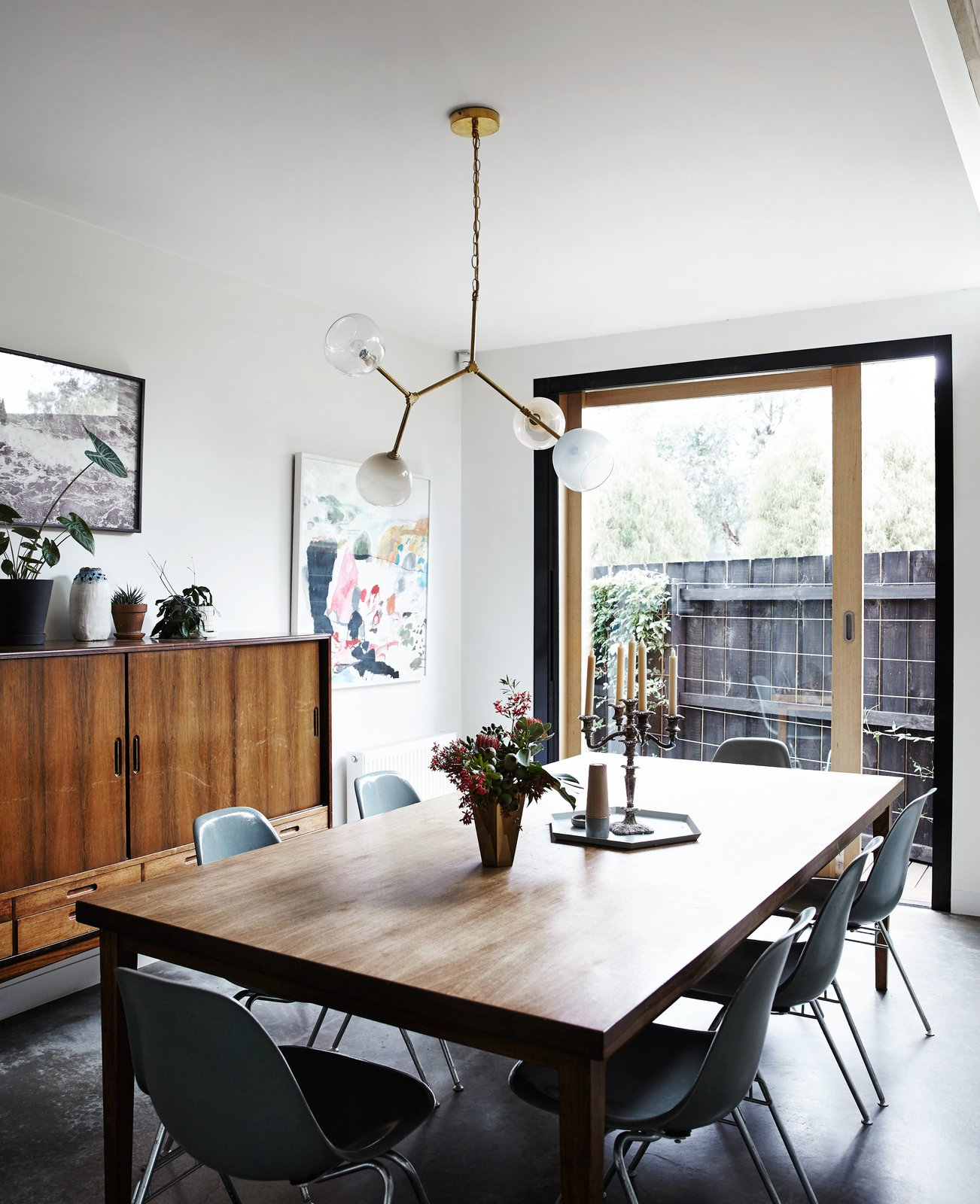 A Y chandelier by Douglas and Bec hangs above a vintage table and chairs.  Photo 6 of 13 in An Unassuming Edwardian Saves the Best for Out Back