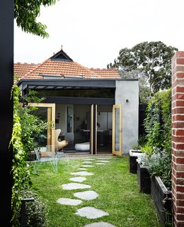 An Unassuming Edwardian Saves the Best for Out Back - Photo 8 of 12 -  On the back facade, cement render and black-painted steel update the existing terra-cotta roof tiles. Custom glass doors fabricated by TCM Building Group open onto the garden, where a stone path leads to a new building housing Kate's studio and Tom's wine cellar.