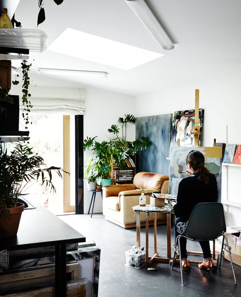 Its timber shiplap cladding tops a concrete blockwork base. Kate uses the main floor as an art studio, where light through a custom skylight illuminates her work space.
