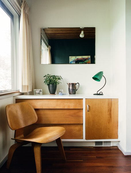 Built-in details include a dresser that pairs with an Eames molded plywood lounge chair in a guest bedroom.