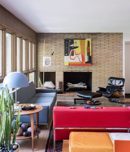 In the living room, a vintage Paul McCobb sofa, a Gio Ponti side table, and an Eames lounge echo the home's midcentury architecture—as does the thrifted red Florence Knoll Parallel Bar sofa that lends the room a shot of color.