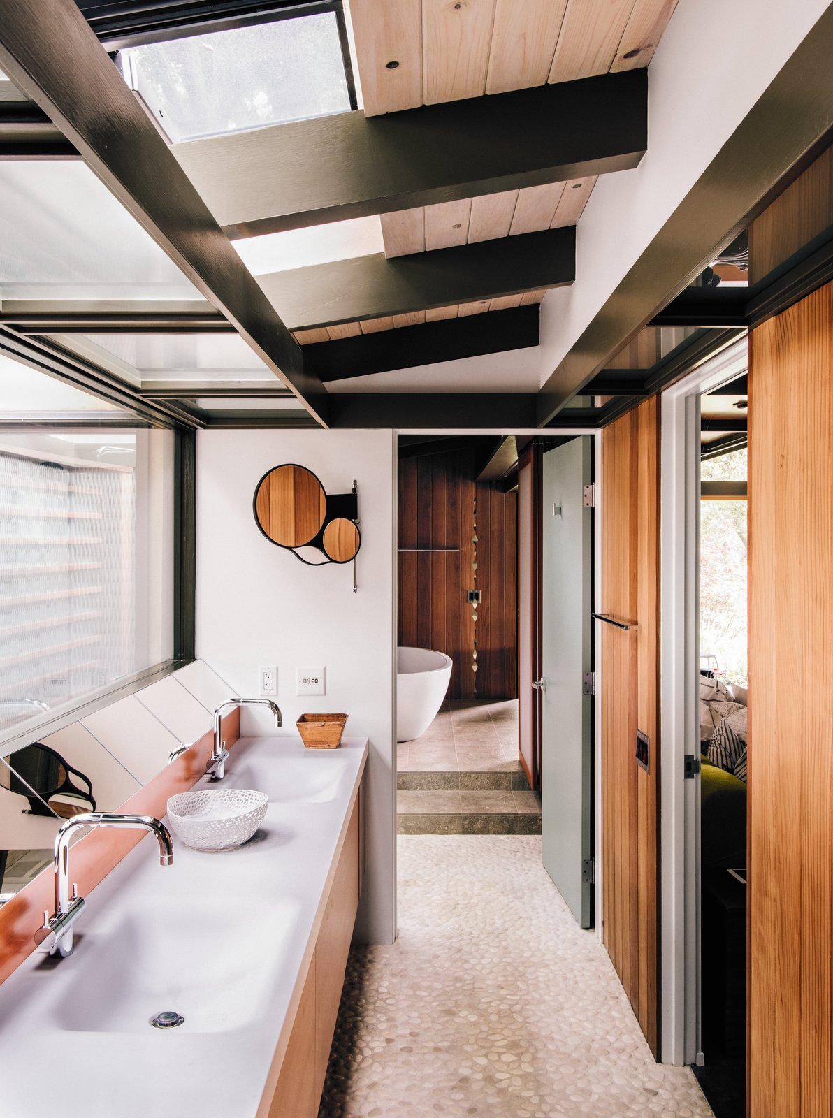 Fung + Blatt designed the master bathroom vanity, which features Agape washbasins and fixtures and an angled mirror that reflects the oak trees seen through the skylights. Tagged: Bath Room and Freestanding Tub.  Photo 5 of 14 in Creative Revival of a Modernist Gem
