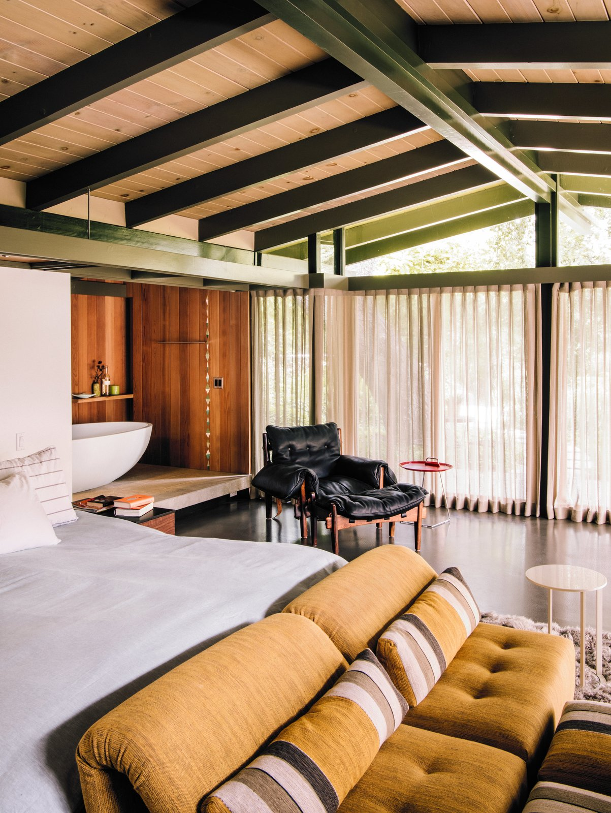 A tub zone lined in redwood connects to the master bedroom, which is furnished with a vintage Sergio Rodrigues lounge chair and Voyage Immobile seats from Roche Bobois.  47+ Midcentury Modern Homes Across America by Luke Hopping from Creative Revival of a Modernist Gem