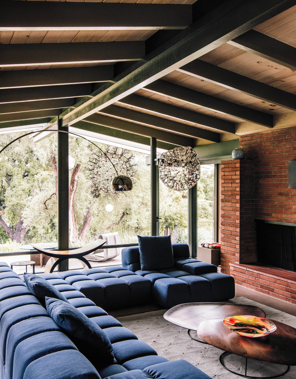 The architects maintained the midcentury post-and-beam construction and Japanese-inspired details of the original building, while brightening and expanding the interior living spaces. Patricia Urquiola's Tufty-Time sofa for B&B Italia meets Pebble coffee tables by Nathan Yong for Ligne Roset in the living room.  Photo 12 of 14 in Creative Revival of a Modernist Gem