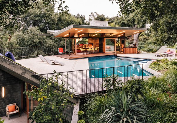 Rising from the edge of the pool deck, a planted overhang shelters a gym and sauna below.