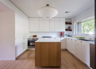 """American Beauty - Photo 4 of 8 - <span style=""""line-height: 1.8;"""">A 1980s renovation dated the kitchen,</span>so Chris integrated a modern white design with a custom island. The oven is by IKEA; other major appliances were purchased from the Habitat for Humanity ReStore."""
