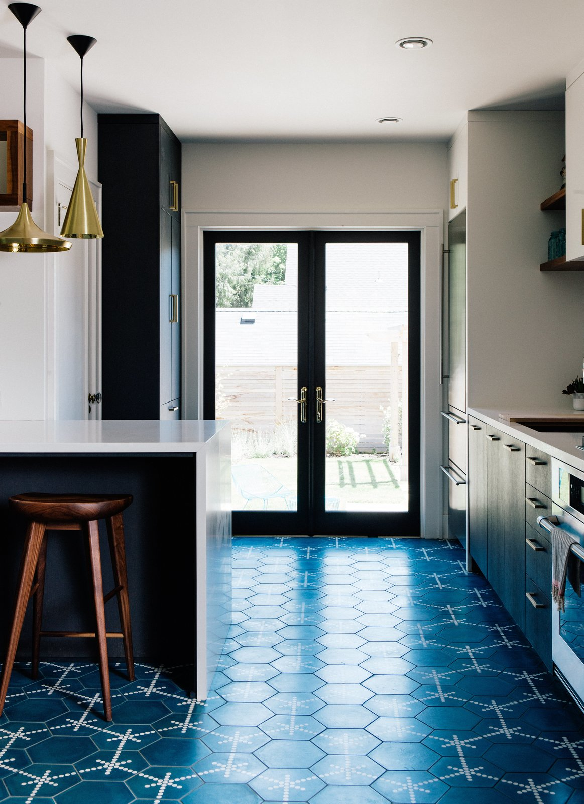 Vintage lover Sarah Benson worked with local firm Bright Designlab to gently update her 1925 home in Portland, Oregon. In the kitchen, Moroccan cement tiles featuring a blue Hex Dot pattern by Popham Designs cover the floor. Tagged: Kitchen, Engineered Quartz Counter, Cement Tile Floor, and Pendant Lighting.  Photo 2 of 10 in A 1925 Portland Home Is a Rad Mashup of 20th-Century Styles