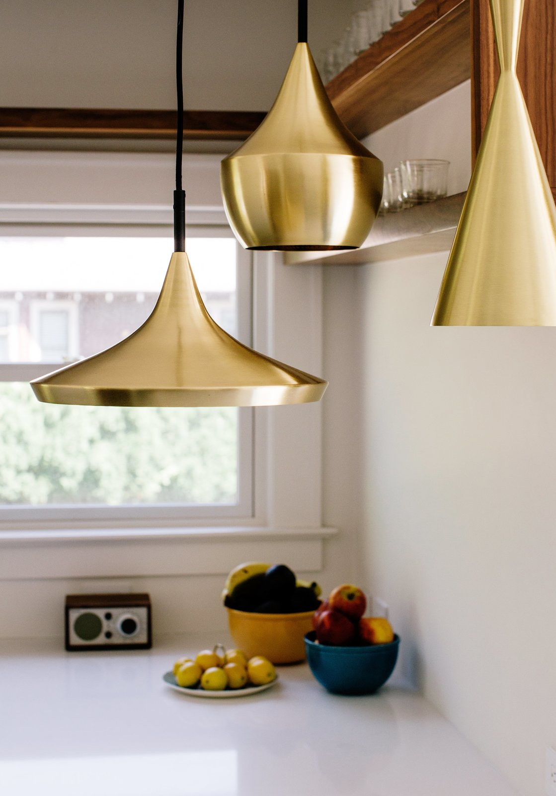 Brass pendants by Tom Dixon hang in the kitchen. A 1925 Portland Home Is a Rad Mashup of 20th-Century Styles - Photo 4 of 10