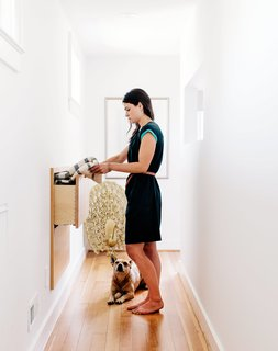 A 1925 Portland Home Is a Rad Mashup of 20th-Century Styles - Photo 4 of 9 - Sarah accesses a custom storage unit in the hallway, an addition that made use of a space behind the wall.